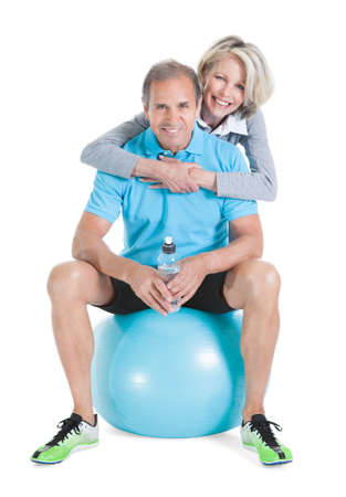 Woman Embracing Mature Man From Behind Sitting On Pilates Ball photo