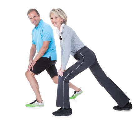 knee bend: Happy Mature Couple At Gym In Fitness Attire Exercising On White Background