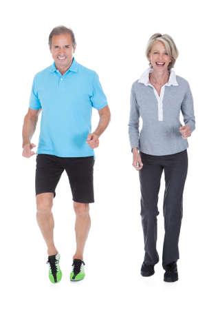 hacer footing: Feliz pareja jogging maduro sobre el fondo blanco