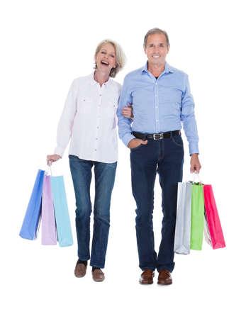 白い背景の上のマルチ色の買い物袋を保持している幸せな成熟したカップル