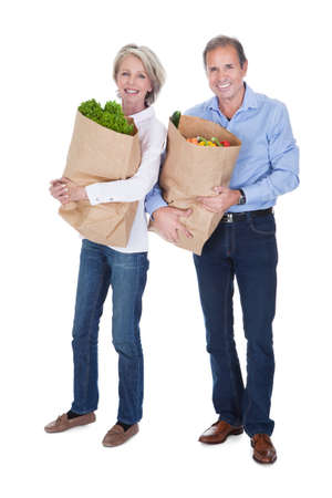 Happy Mature Couple Shopping Fresh Vegetable Over White Background photo