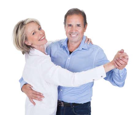 白い背景の上に分離踊る幸せな成熟したカップル