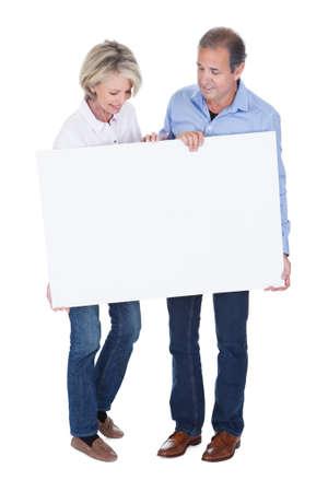persona: Feliz pareja madura que sostiene el cartel en blanco aislado más de fondo blanco Foto de archivo