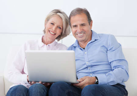 Happy Mature Couple Sitting On Couch And Working On Laptop photo