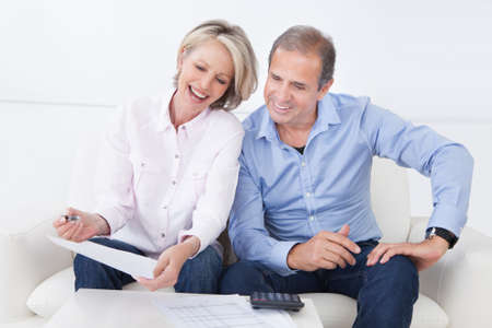 retirement  age: Portrait Of A Couple Sitting On Couch Enjoying Success