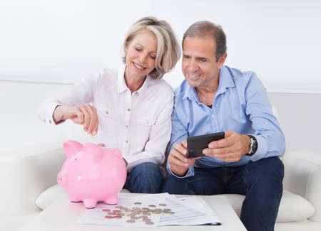 의 piggybank에 동전을 계산 성숙한 행복한 커플
