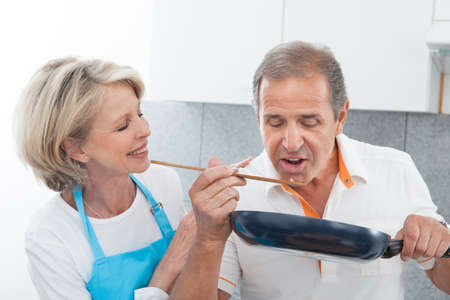 Man Looking At Woman Cooking Food In Kitchen photo