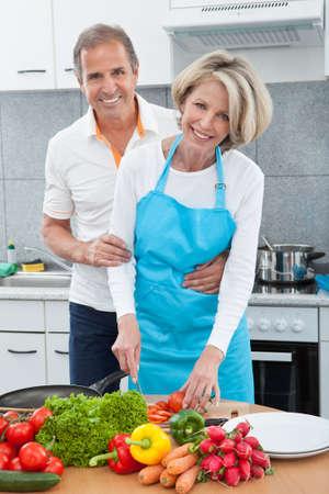 aceite de cocina: El hombre mira a la mujer que prepara el alimento en la cocina Foto de archivo