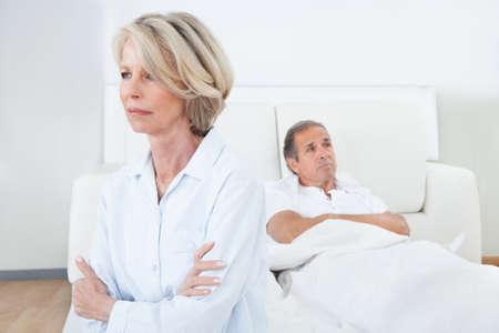 Mujer triste sentada en el borde de la cama delante de Man