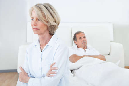 mature male: Sad Woman Sitting At The Edge Of Bed In Front Of Man