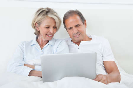 both: Portrait Of Happy Mature Couple On Bed Using Laptop Stock Photo