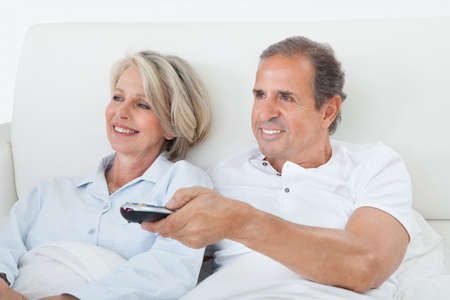 Happy Senior Couple Lying On Bed Watching Television photo