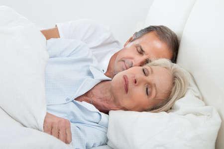 pareja durmiendo: Retrato de la feliz pareja senior dormir juntos en la cama