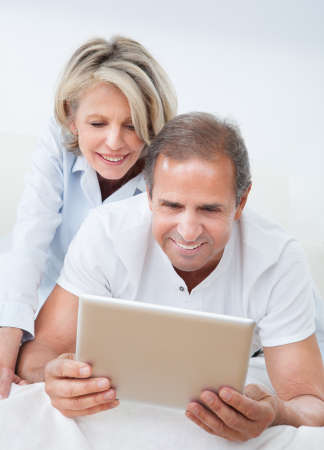 Happy Mature Man Using Digital Tablet Woman Looking From Behind photo