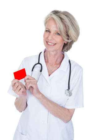 Mature Female Doctor Holding Visiting Card Over White Background photo