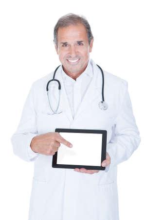 Reife männlichen Arzt hält Tablet PC auf weißem Hintergrund