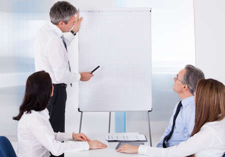 classroom training: Group Of Business People Appreciating Businessman At Presentation