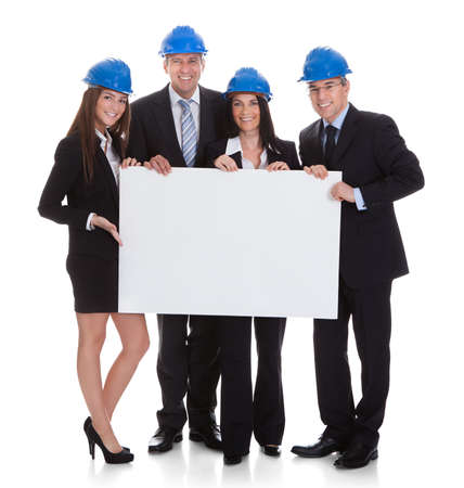 hardhat: Group Of Happy Architects Holding Blank Placard Over White Background Stock Photo