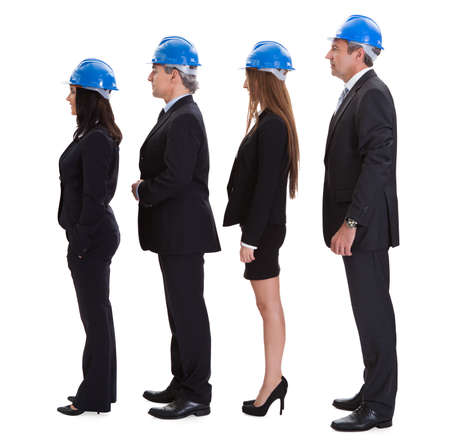 Group Of Happy Architects Standing In A Row Over White Background photo
