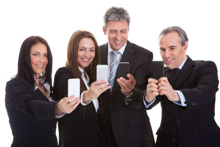 Happy Business People Looking At Cell Phones Over White Background photo