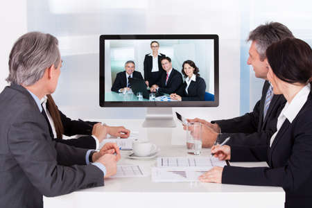 presentation screen: Group Of Businesspeople In Video Conference At Business Meeting