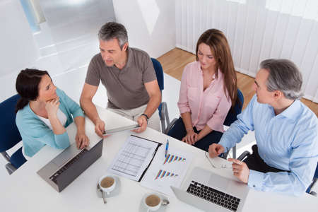 casual meeting: Portrait Of Happy Business People Working Together Stock Photo