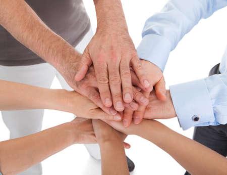manos unidas: Primer plano de la mano apilados unos sobre otros en el fondo blanco