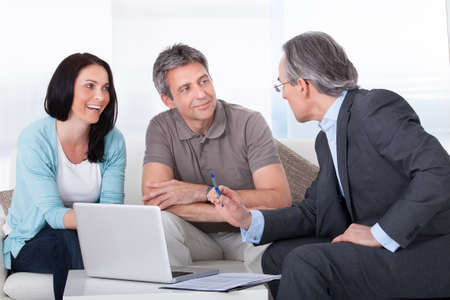 Happy Couple And Mature Consultant Discussing Together Stock Photo