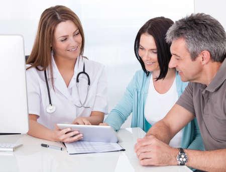 paciente: Feliz pareja en la tableta digital en poder de doctor