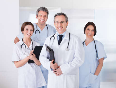 healthcare: Male Doctor Standing In Front Of Team Using Digital Tablet