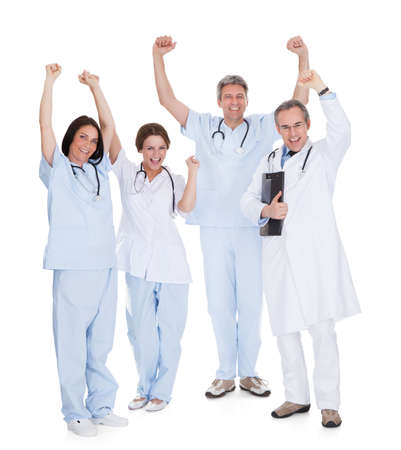 Group Of Happy Excited Doctors With Arm Raised Isolated Over White Background photo