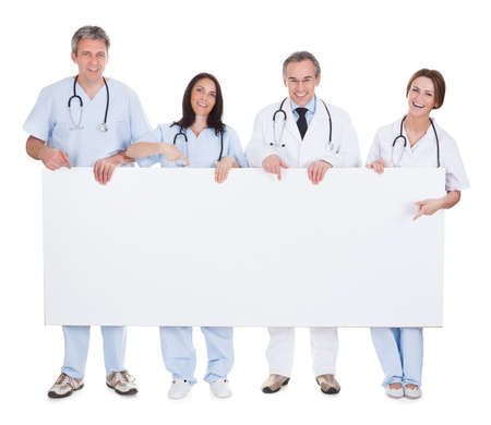 Group Of Happy Doctor Standing In A Row Holding Placard photo