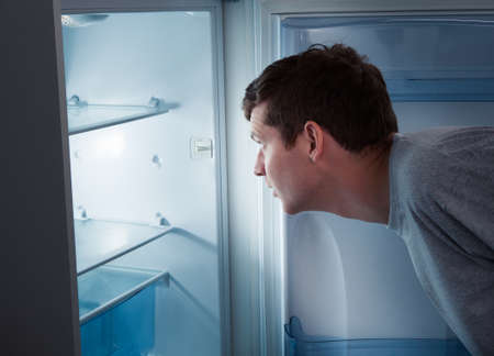 Portrait of a hungry man looking for food in refrigerator