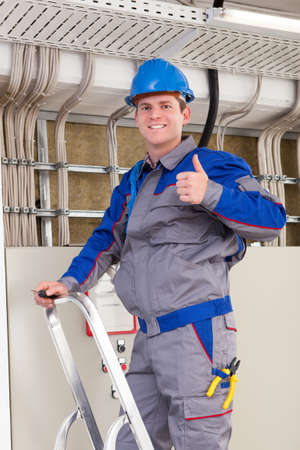 Young Worker Man With Hard Hat standing on ladder photo
