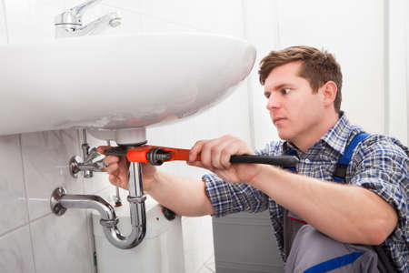 plumber: Portrait of male plumber fixing a sink in bathroom