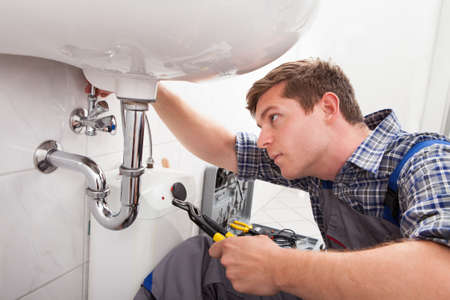 plumbing: Portrait of male plumber fixing a sink in bathroom