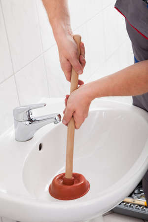 clog: Portrait of male plumber pressing plunger in sink