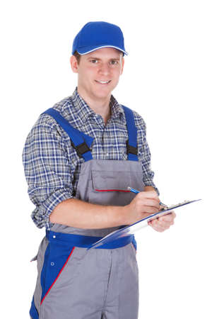 tradesmen: Young construction worker writing on clipboard isolated on white background Stock Photo