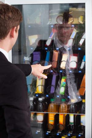 distributeur automatique: Homme se dirigeant � chocolat dans le g�teau d'affichage