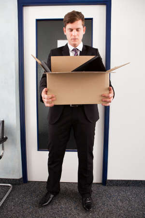 moving office: Portrait of young businessman holding cardboard in office Stock Photo