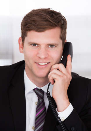 Portrait of businessman talking on telephone in office Stock Photo - 20984120