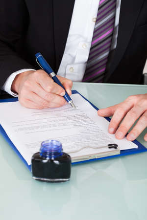 Close-up Of Businessman Hand Writing With Ink Pen Over Document photo