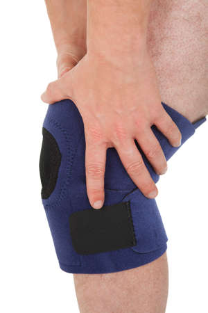 Close-up Of A Man Wearing Knee Brace Over White Background photo