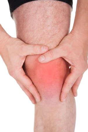 artrosis: Hombre con dolor de rodilla en el fondo blanco Foto de archivo