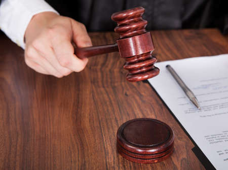 Close-up Of Male Judge Hand Striking The Gavel In A Courtroom photo