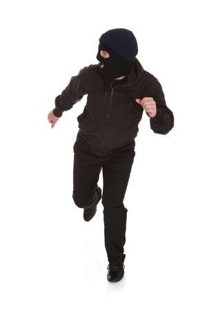 白い背景の上を実行しているマスクを着た男 写真素材