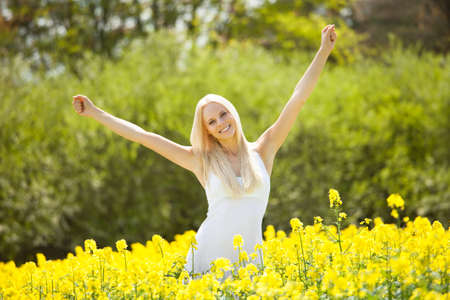 arm extended: Happy Young Woman Amid With Flowers In Field Stock Photo