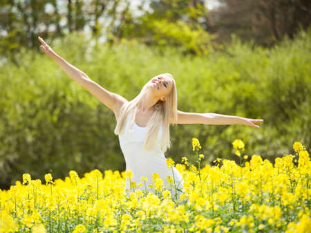 Smiling Relaxed Young Woman Amid With Flowers In Field photo