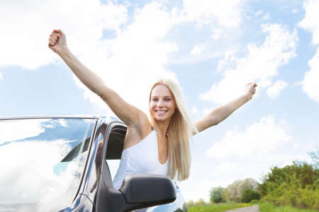 Happy Young Woman Raising Hand Out Of Car Window photo