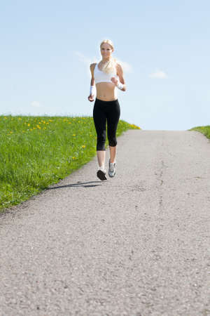 Portrait Of Young Healthy Woman Jogging In Park photo